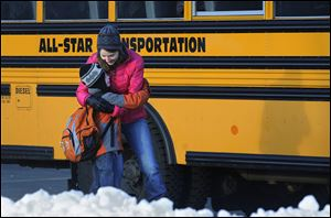 A woman hugs a child before he boards a bus on the first day of classes after the holiday break, in Newtown, Conn. Children from Sandy Hook Elementary School returned to school in the neighboring town of Monroe.