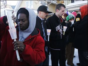 Friends, including Devon Smith, left, attend a candlelight vigil for Brian Minley, Jr.