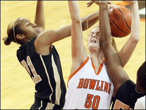 Bowling Green State University's Miriam Justinger gets an arm in the cheek while being defended by UCF's Kiana Morton, left, and Erika Jones, right.