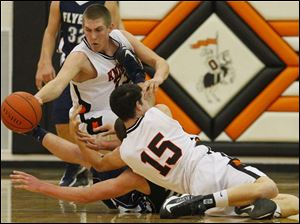 Otsego's senior Ryan Smoyer (23) reaches for a loose ball after his teammate senior Jerome Griffin (15) hit the floor with a Lake defender.