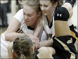 Sylvania Northview's Maddie Cole (44), left, and Maddie Fries (4) battle Perrysburg's Allex Brown (35) for a loose ball.