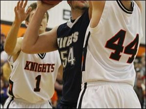 Lake's senior Marcus Pierce (54) goes up for two points against Otsego's senior Tommy Rodgers (1) and junior John Thomas (44).