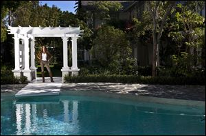 Morgan Brown poses at a luxury home in Los Angeles, California, in, that she bought, fixed up and is trying to flip.