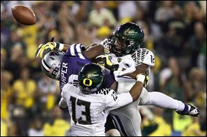 Oregon's Brian Jackson (12) and Troy Hill (13) break up a pass intended for Kansas State's Chris Harper.