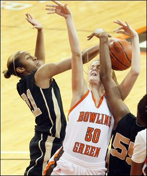 Bowling Green State University's Miriam Justinger gets an arm in the face while being defended by UCF's Kiana Morton, left, and Erika Jones.