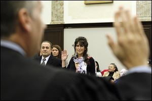 Tia Weber, from Georgia, center, is sworn in by Judge Jeffrey J. Helmick during the naturalization ceremony in U.S. District Court. At left is Hesham Moris Ibrahim Youssef of Egypt.
