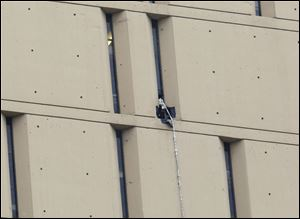 A rope dangles from a window on the back side of the Metropolitan Correctional Center, where two convicted bank robbers used a knotted rope or bed sheets to escape from the federal prison window high above downtown Chicago.
