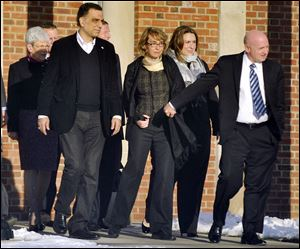 Former U.S. Rep. Gabrielle Giffords, center, holds hands with her husband, Mark Kelly, while exiting Town Hall at Fairfield Hills Campus today in Newtown, Conn.