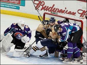 Orlando Solar Bears' goalie John Curry, left, looks back as a mixture of Walleye and Solar Bears are in the net.