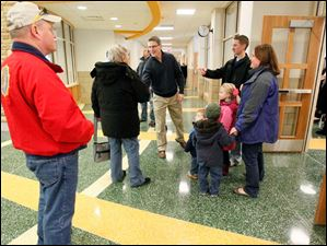 Brad Rieger, center, superintendent of Sylvania Schools, greets visitors.