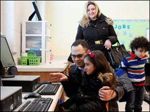 Mohammad El-Sayyad, left, looks at the new computers with his daughter Lea El-Sayyad, 7, in her kindergarten room. Mother Mona El-Sayyad, back and her brother Adam El-Sayyad, 5, right, also look on.