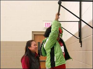 Grace Davis, left, watches as her sister Eliza Jane Davis,7, tries out the chin-up bar in the new gymnasium.
