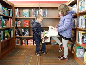 Students Jacob Phillips, 5, left, and his sister Shaina Phillips, 8, right, check out the books in the new multimedia/library.