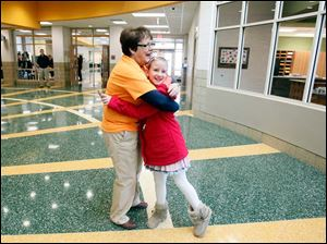 Toni Gerber, principal, hugs third grader Madison Taylor while she welcomed students and families to tour the new school.