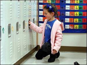 Molly Rogers, 5, tries out her new locker in the kindergarten room.
