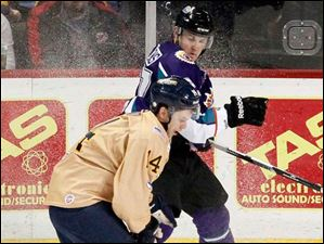 Toledo Walleye's Joey Martin and Orlando Solar Bears' Dan Dries fight for the puck.