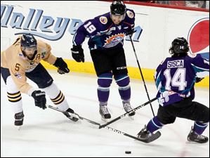 Toledo Walleye Wes O'Neill tries to get the puck before from Orlando' Solar Bears' Dan Gendur, No. 19, and Mathew Sisca.
