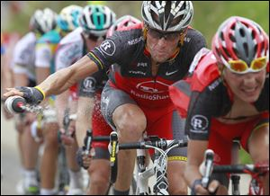 Lance Armstrong throws out his water bottle in the last kilometers of the climb toward Station les Rousses, France, during the seventh stage of the Tour de France cycling race.