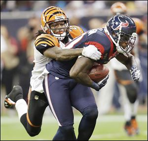 Texans wide receiver Andre Johnson is tackled by Bengals cornerback Adam Jones in the third quarter of Saturday's AFC wild-card playoff game. Houston advances to play at New England.