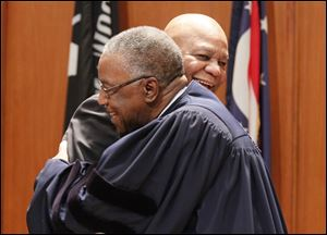 Toledo Municipal Court Judge C. Allen McConnell, front,  embraces Phil Copeland after he swore him in as Lucas County recorder at One Government Center.