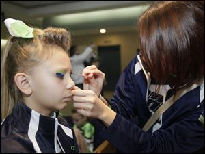 Kayla Knight, 9, of Toledo is readied for performing by a fellow member of the Ohio Elite All Stars, Megan Richardville, 17, of Walbridge. The team is from Milbury.