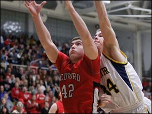 Whitmer's Nate Holley (34) battles Bedford's Jeremiah Harris (42) for a rebound.