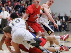 Whitmer's Ricardo Smith (10) lands on Bedford's Adam Swisher (15) as they and Whitmer's Nate Holley (34) and Bedford's Dylan Barr (24) battle for the ball.