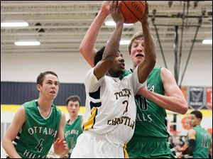Toledo Christian's Dominique Pittman (3) drives to the net against Ottawa Hills' RJ Coil (40).