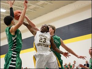 Toledo Christian's Melvin Thomas (23) is surrounded by Ottawa Hills' AJ King (11) and RJ Coil (40).