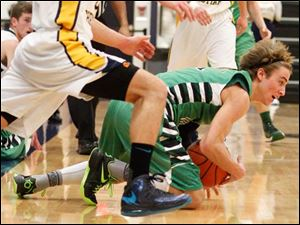 Toledo Christian's Eric Cellier (5) defends as Ottawa Hills' Blake Pappas (1) goes to the ground to hold on to the ball.