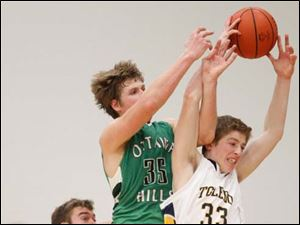 Toledo Christian's Kyle Kempton (33) battles Ottawa Hills' Lucas Janowicz (35) for possession of the ball.