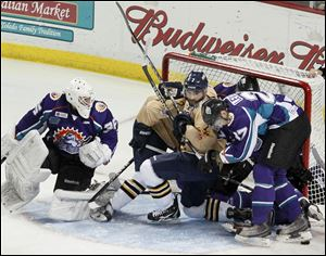 Orlando goaltender John Curry looks back as Walleye and Solar Bears collide into the net in Saturday night's game at the Huntington Center.