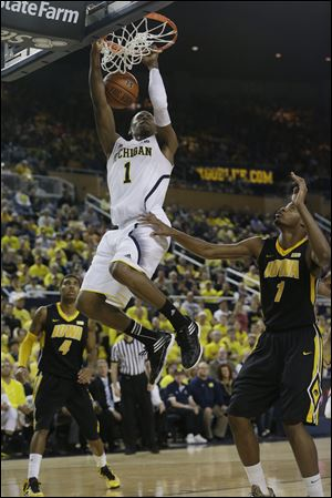 Michigan forward Glenn Robinson III dunks over Iowa forward Melsahn Basabe during the second half Sunday at Crisler Arena i