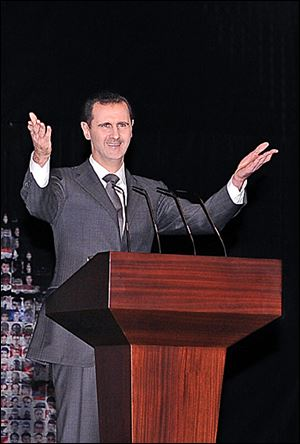 Syrian President Bashar Assad speaks to a cheering, chanting crowd at the Opera House in central Damascus. He offered a new peace plan during Sunday's address.