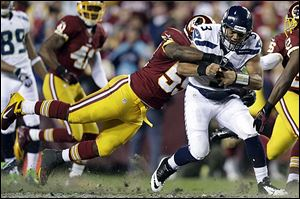 The Seahawks' Russell Wilson drags the Redskins' London Fletcher during a play in the first half. Washington faltered down the stretch as the rookie Wilson led Seattle to a playoff win.