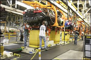 A drive train assembly is mated to a Buick Verano at the Orion Assembly plant in Orion Township, Mich. Nearly four years after GM filed for bankruptcy protection, the automaker is building the Verano and the Sonic, the best-selling subcompact car in the nation.