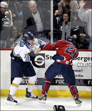 Toledo's Travis Novak, left, fights with Kalamazoo's Dustin Cloutier during Sunday's game with the Wings.