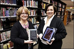 Jodi Russ, left, community librarian, displays a Nook Color, and circulation clerk Jennifer Wenzel holds an iPad at the Bedford Branch Library. The library has scheduled more ereader classes.
