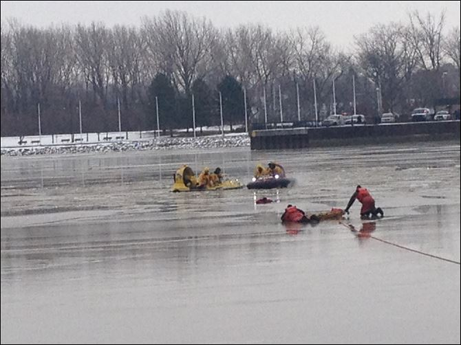 firefighers, coast guard rescue Washington Township firefighters and members of the Coast Guard work to rescue a woman from the ice on the Maumee River.