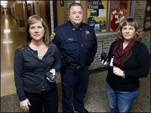 Cari Buehler, left, assistant Genoa High School principal, Terry Mitchell, Clay Township police chief, and  Brenda Murphy, Genoa Elementary School principal, have radios that will provide immediate contact with administrators campuswide and law enforcement in the event of an emergency.
