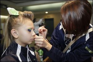 Kayla Knight, 9, of Toledo, is prepped for the performance by Megan Richardville, 17, of Walbridge, a fellow member of the Ohio Elite All Stars.