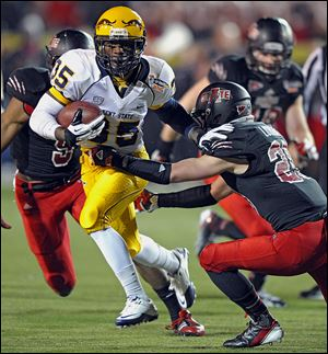 Kent State tailback Julian Durden, left, evades Arkansas State's Cole Lorigan during the GoDaddy.com Bowl on Sunday.