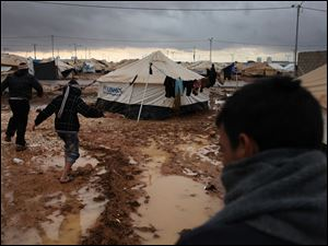 Syrian refugees make their way on water and mud, at Zaatari Syrian refugee camp, near the Syrian border in Mafraq, Jordan, Tuesday, Jan. 8, 2013. Syrian refugees in a Jordanian camp attacked aid workers with sticks and stones on Tuesday, frustrated after cold, howling winds s