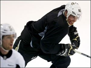 Pittsburgh Penguins captain Sidney Crosby (87) begins a rush up ice behind James Neal during an informal workout with a dozen of the NHL hockey team's players in Pittsburgh, Monday.