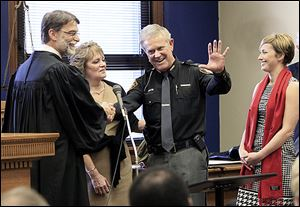 Lucas County Judge Dean Mandros, left, and Phyllis Tharp smile after Maj. John Tharp, becomes the county's newest sheriff. The Tharps' daughter, Kati, right, looks on. An overflow crowd was on hand for Monday's ceremony at the Lucas County Courthouse.