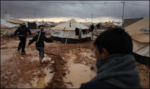 Syrian refugees make their way on water and mud, at Zaatari Syrian refugee camp, near the Syrian border in Mafraq, Jordan, Tuesday, Jan. 8, 2013. Syrian refugees in a Jordanian camp attacked aid workers with sticks and stones on Tuesday, frustrated after cold, howling winds swept away their tents and torrential rains flooded muddy streets overnight. Police said seven aid workers were injured. (AP Photo/Mohammad Hannon)