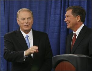 Former Ohio Gov. Ted Strickland, left, and current Gov. John Kasich acknowledge supporters following their debate at the University of Toledo in October, 2010.
