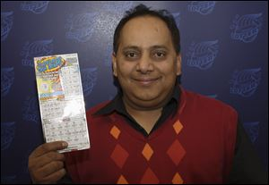 Urooj Khan, 46, of Chicago's West Rogers Park neighborhood, poses with a winning lottery ticket.