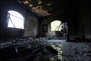 A Libyan man investigates the inside of the U.S. Consulate after an attack that killed four Americans, including Ambassador Chris Stevens, on the night of Tuesday, Sept. 11, 2012, in Benghazi, Libya.
