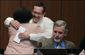 Councilwoman Paula Hicks-Hudson hugs Shaun Enright after he was appointed as the new member of Toledo City Council during a vote at Council Chambers at Government Center in Toledo. At right is councilman Steven C. Steel.